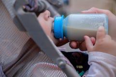 A mãe está alimentando o bebê de uma garrafa fora, vídeo do close-up fotografia de stock