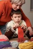 A mãe está aprendendo seu menino da criança fazer malha Os fios de lãs coloridos estão na tabela de madeira foto de stock