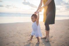 A mãe está ensinando suas caminhadas da filha na praia fotos de stock royalty free