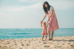 A mãe está ensinando suas caminhadas da filha na praia fotografia de stock