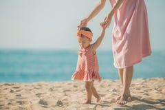 A mãe está ensinando suas caminhadas da filha na praia fotos de stock