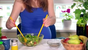 A mãe expectante derrama o sal e mistura a salada ecológica dos vegetais na bacia de vidro filme