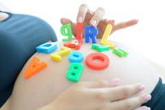 A mãe expectante nova com letra obstrui a menina da soletração em sua barriga grávida Fotografia de Stock Royalty Free