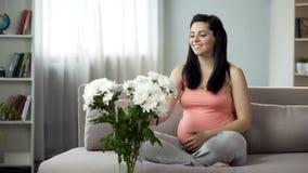 A mãe expectante que admira o ramalhete bonito das flores apresentou pelo marido fotografia de stock royalty free