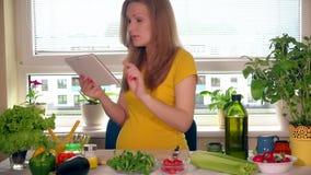Mãe expectante que procura os ingredientes vegetais da salada usando o tablet pc vídeos de arquivo