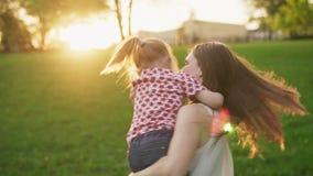 A mãe feliz abraça a filha pequena adorável e gerencie com ela no parque ensolarado video estoque