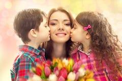 Mãe feliz beijada por seus filha e filho Fotos de Stock Royalty Free