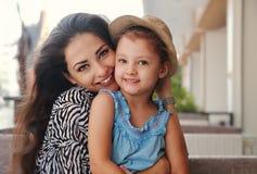 Mãe feliz bonita que abraça a indoo de sorriso joying da filha fotografia de stock royalty free