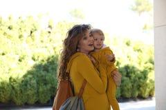 Mãe feliz com a criança no olhar da família da roupa elegante em um parque foto de stock