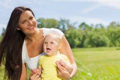 Mãe feliz com a criança no prado verde Fotografia de Stock Royalty Free