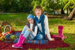 Mãe feliz com a filha pequena no parque do outono Imagens de Stock