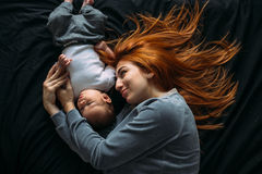 Mãe feliz com o bebê que encontra-se junto na cama Fotos de Stock Royalty Free