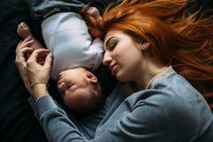 Mãe feliz com o bebê que encontra-se junto na cama Foto de Stock