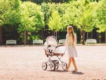 Mãe feliz com o carrinho de criança no parque Fotografia de Stock