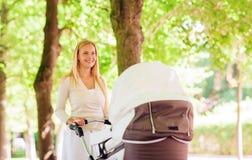 Mãe feliz com o carrinho de criança no parque Imagens de Stock Royalty Free