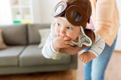 Mãe feliz com o chapéu piloto vestindo do bebê em casa fotografia de stock