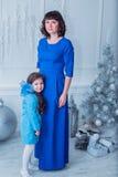A mãe feliz com sua filha em vestidos azuis longos está perto da árvore de Natal Imagens de Stock