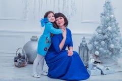 A mãe feliz com sua filha em vestidos azuis longos está perto da árvore de Natal Fotografia de Stock