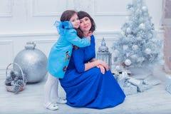 A mãe feliz com sua filha em vestidos azuis longos está perto da árvore de Natal Imagens de Stock Royalty Free
