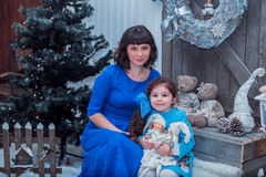 A mãe feliz com sua filha em vestidos azuis longos está perto da árvore de Natal Fotos de Stock