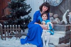 A mãe feliz com sua filha em vestidos azuis longos está perto da árvore de Natal Foto de Stock Royalty Free