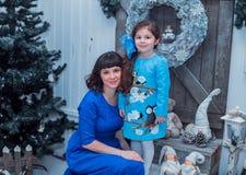 A mãe feliz com sua filha em vestidos azuis longos está perto da árvore de Natal Imagem de Stock Royalty Free