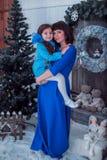 A mãe feliz com sua filha em vestidos azuis longos está perto da árvore de Natal Imagem de Stock