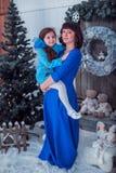 A mãe feliz com sua filha em vestidos azuis longos está perto da árvore de Natal Foto de Stock