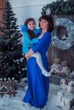 A mãe feliz com sua filha em vestidos azuis longos está perto da árvore de Natal Fotografia de Stock Royalty Free