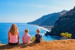 Mãe feliz, crianças no monte com opinião cênico dos penhascos do mar imagens de stock