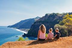 Mãe feliz, crianças no monte com opinião cênico dos penhascos do mar fotografia de stock