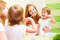 Mãe feliz da família e criança da filha que escova seu toothb dos dentes fotos de stock royalty free