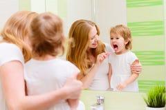 Mãe feliz da família e criança da filha que escova seu toothb dos dentes Fotografia de Stock