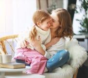 Mãe feliz da família e filha de amor da criança que abraça pela janela imagens de stock