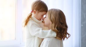 Mãe feliz da família e filha de amor da criança que abraça pela janela fotografia de stock