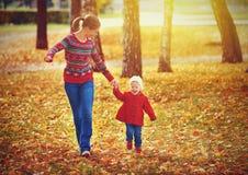 A mãe feliz da família e a filha pequena da criança no outono andam