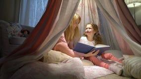 Mãe feliz da família e sua filha pequena que leem um livro em uma barraca em casa filme