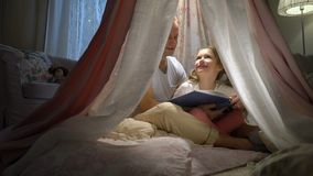 Mãe feliz da família e sua filha pequena que leem um livro em uma barraca em casa video estoque