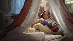 Mãe feliz da família e sua filha pequena que leem um livro em uma barraca em casa vídeos de arquivo