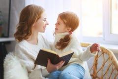 A mãe feliz da família lê o livro à criança à filha pela janela fotografia de stock