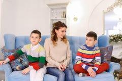 A mãe feliz de dois filhos e irmãos dos meninos senta-se de lado a lado e Foto de Stock