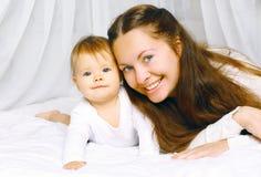 Mãe feliz do retrato e bebê bonito na casa da cama foto de stock