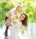 Mãe feliz do retrato e filha de sorriso da criança que tem o divertimento Imagens de Stock Royalty Free
