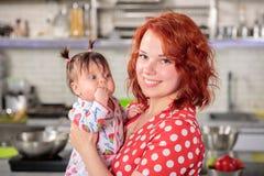 Mãe feliz do ruivo com pouco doughter nas mãos fotografia de stock royalty free