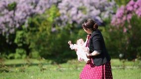 Mãe feliz e bebê bonito que jogam junto em um parque contra flores filme