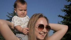 Mãe feliz e bebê que andam fora no dia de verão