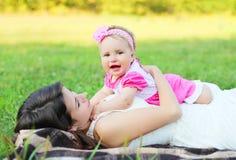 Mãe feliz e bebê que encontram-se junto na grama no verão Fotografia de Stock Royalty Free