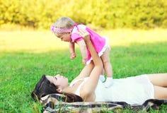 Mãe feliz e bebê que encontram-se junto na grama que tem o divertimento no verão Imagens de Stock
