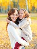 Mãe feliz e criança de sorriso que têm o divertimento junto no outono Imagens de Stock
