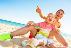 Mãe feliz e criança modernas no litoral que apontam em algo fotografia de stock royalty free